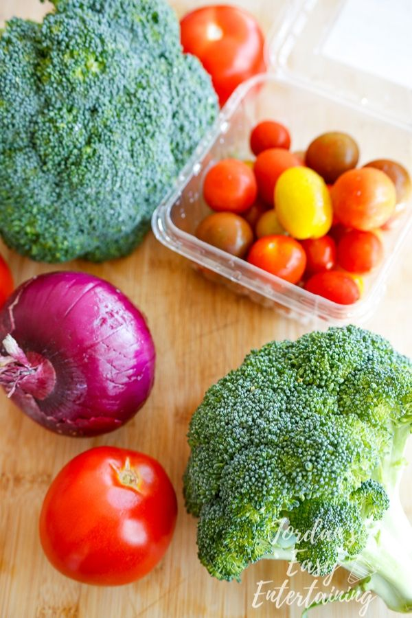 ingredients for an easy side salad made of broccoli, tomato, and red onion