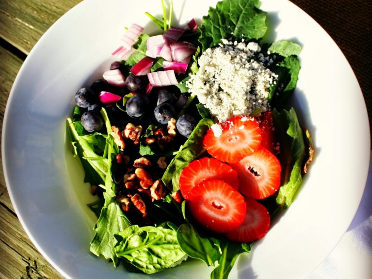 a summer salad made up of fresh spinach, blueberries, strawberries, pecans, red onion, and Gorgonzola cheese in a white salad bowl.