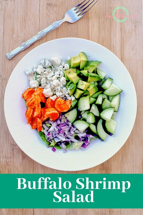 One of the best salad recipes with buffalo shrimp, blue cheese, cucumber, avocado, red onion, and lettuce in a white serving bowl with the text Buffalo shrimp salad