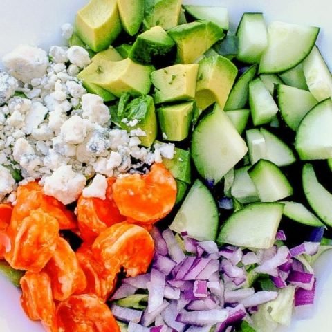 Close up image of Buffalo Shrimp salad with buffalo shrimp, blue cheese, red onion, cucumber, avocado, and lettuce in a white serving dish