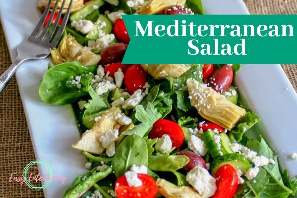 A white serving dish with a Mediterranean salad full of mixed greens, tomato, cucumber, marinated artichoke heart, Kalamata olives, and feta cheese