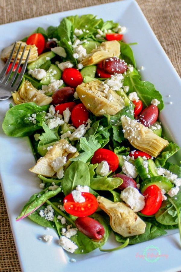 One of the best salad recipes this Mediterranean salad is shown with mixed greens, marinated artichoke hearts, Kalamata olives, tomatoes, cucumbers, and feta cheese