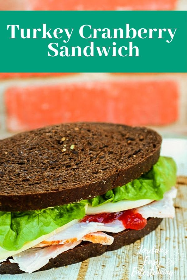 a thanksgiving turkey sandwich with pumpernickle bread, lettuce, and cranberry sauce