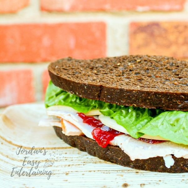 a cold turkey sandwich with cranberry sauce, cheese, and lettuce