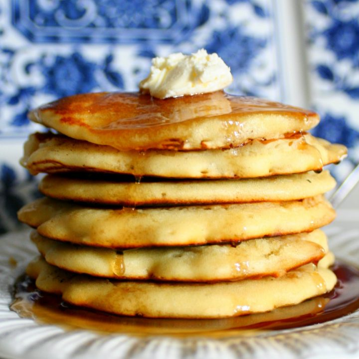 a stack of fluffy buttermilk pancakes with a dollop of whipped homemade butter and hot maple syrup