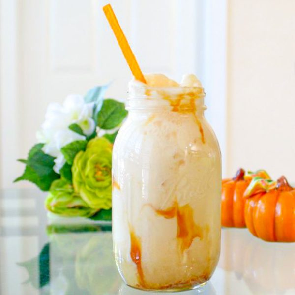 a mason jar with an orange straw and one of the best frozen desserts ever - and apple cider ice cream float with caramel sauce