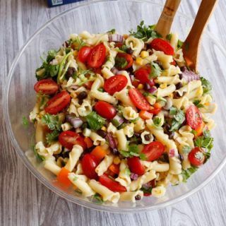 a southwest pasta salad recipe made up of pasta, tomatoes, bell pepper, corn, black beans, and cilantro served in a clear bowl with salad servers