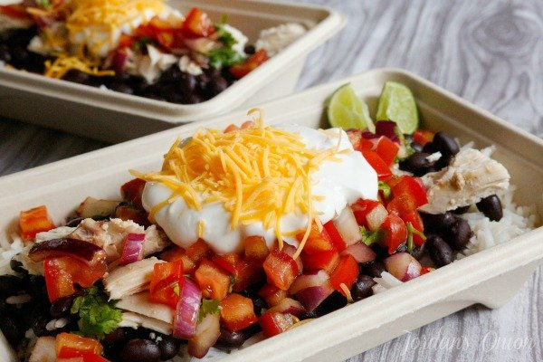 chicken burrito bowls topped with beans, tomato, sour cream and cheese