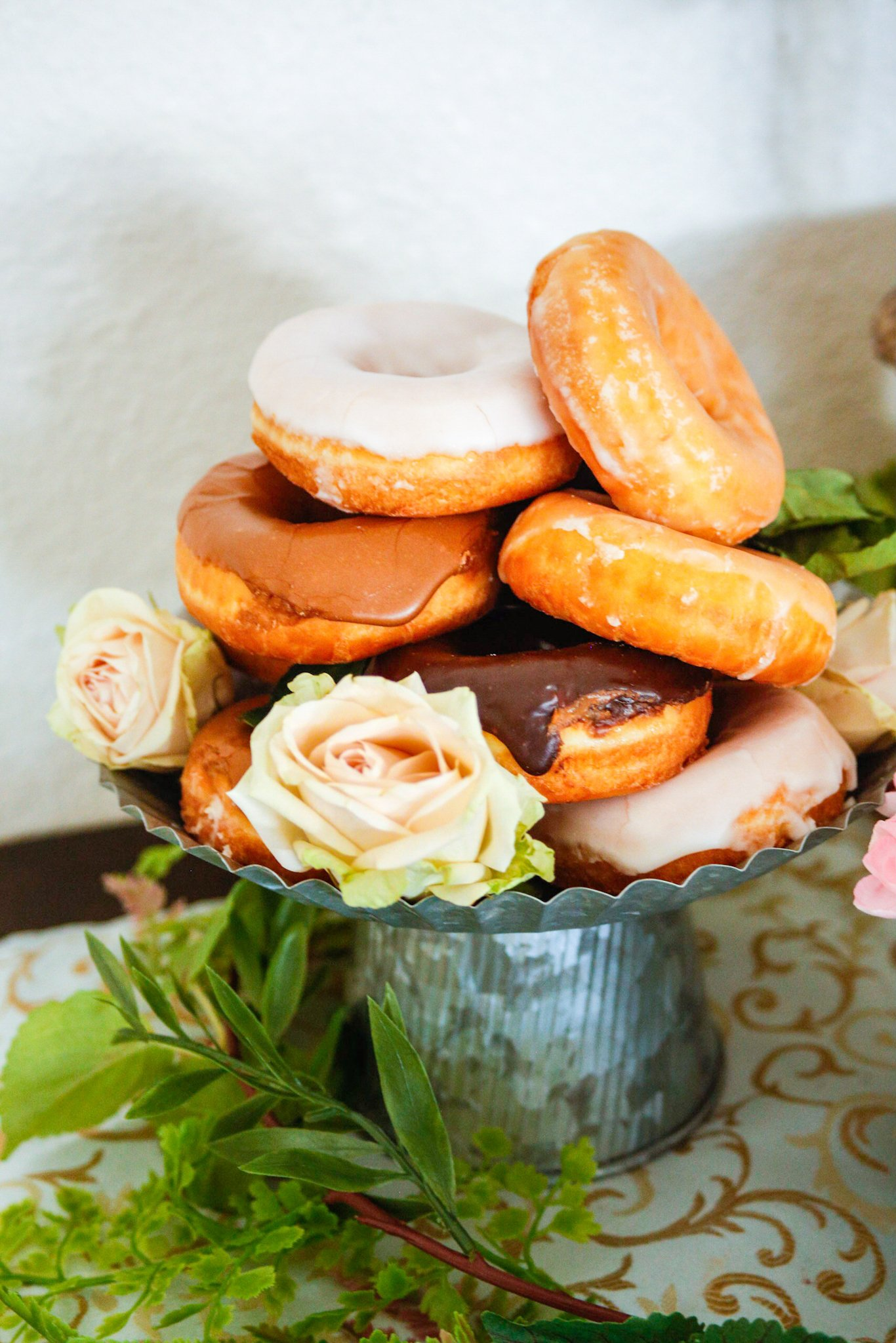 Donuts served on a cake stand with pale pink roses