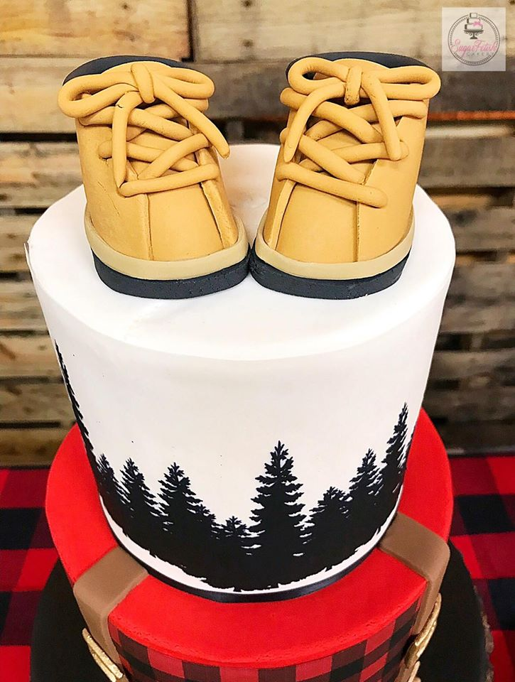 Fondant baby shoes as a cake topper on this lumberjack baby shower cake - see more ideas for this adorable lumberjack baby shower at Jordan's Easy Entertaining - cake by Sugar Fetish Cakery in New Jersey