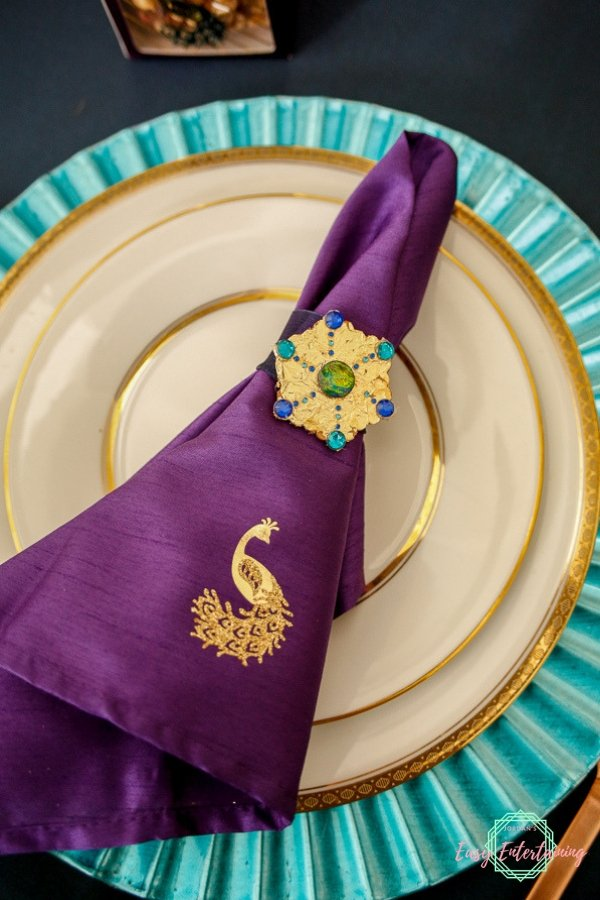 Place setting featuring a gold peacock on a purple napkin with a peacock themed snowflake napkin ring #ad