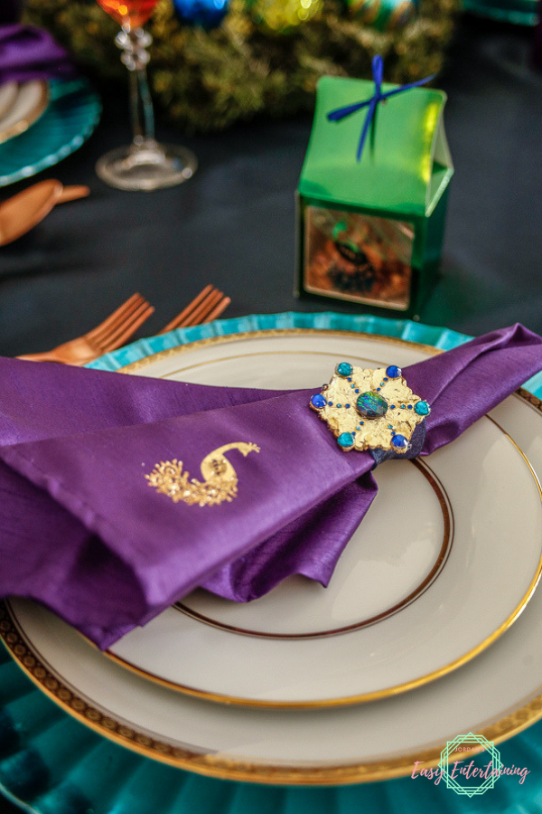 A place setting featuring a purple napkin, gold rimmed china, and green gift box perfect for peacock theme Christmas table decorations #ad #Cricut