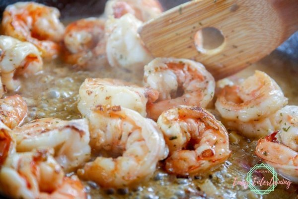 shrimp scampi being sauteed in a cast iron skillet with a wooden spoon