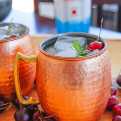 American Mules served in a copper mug with ice, mint, and cherries and a bottle of Smirnoff Red White and Berry vodka in the background