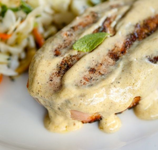 sage mustard cream sauce on top of a grilled pork chop