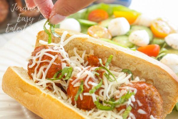 basil going on top of a Italian meatball sub sandwich