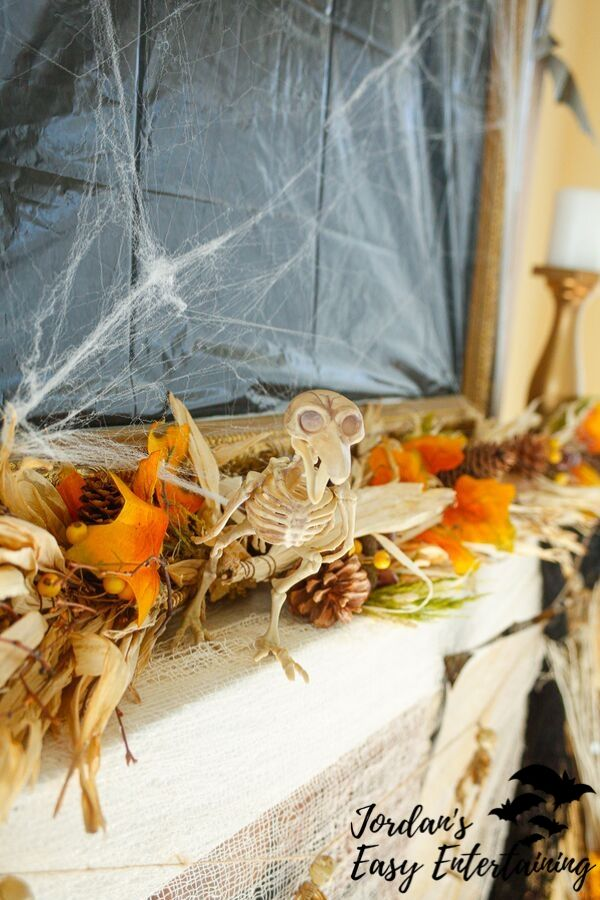 a Dollar Tree skeleton bird on a fireplace mantel with fall garland