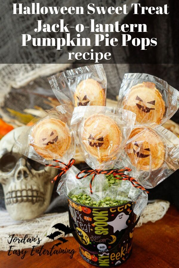 jack-o-lantern pumpkin pie pops on display for a Halloween party dessert table