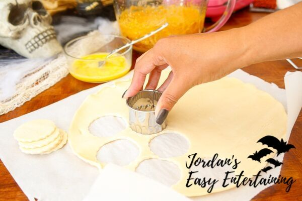 cutting out pie dough to make pumpkin pie pops as a Halloween sweet treat