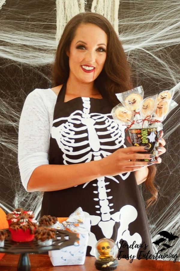 Jordan from Jordan's Easy Entertaining holding up jack-o-lantern pumpkin pie pops with a spooky spiderweb background