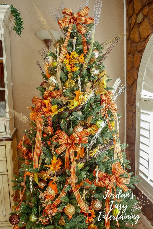 a new favorite Thanksgiving decoration idea - a thankful tree decorated with beautiful fall themed ribbon, ornaments, scarecrows, and fall foliage