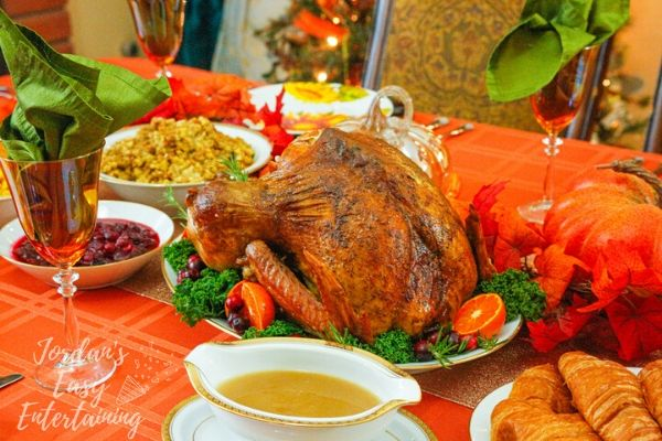A Thanksgiving table set with a roasted turkey and simple side dishes