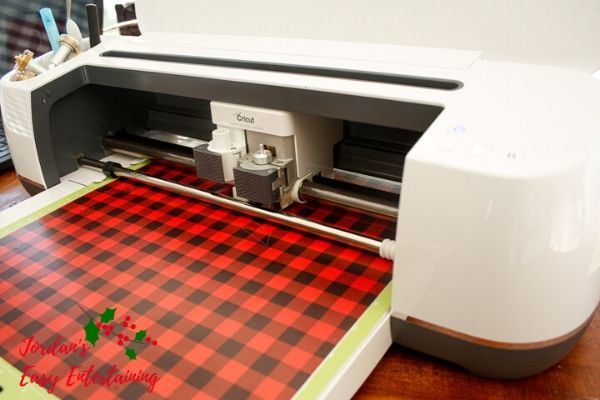 a Cricut Maker machine cutting lumberjack buffalo plaid vinyl