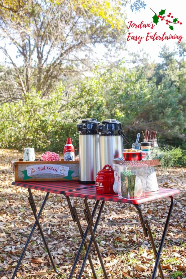 an outdoor hot chocolate bar setup in the woods