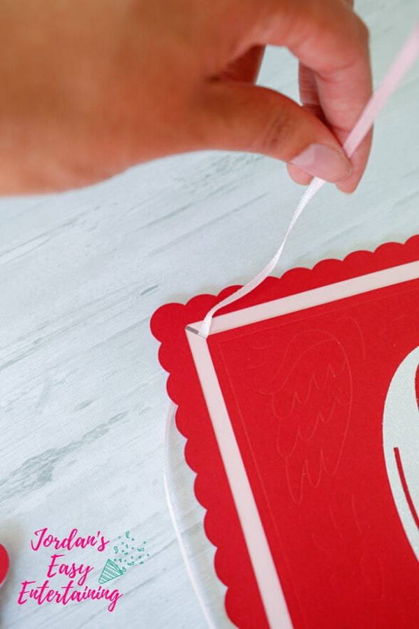 adding ribbon to a diy paper craft party banner