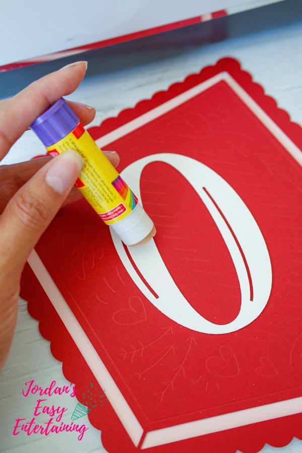 gluing together paper Valentine crafts made with Cricut Maker
