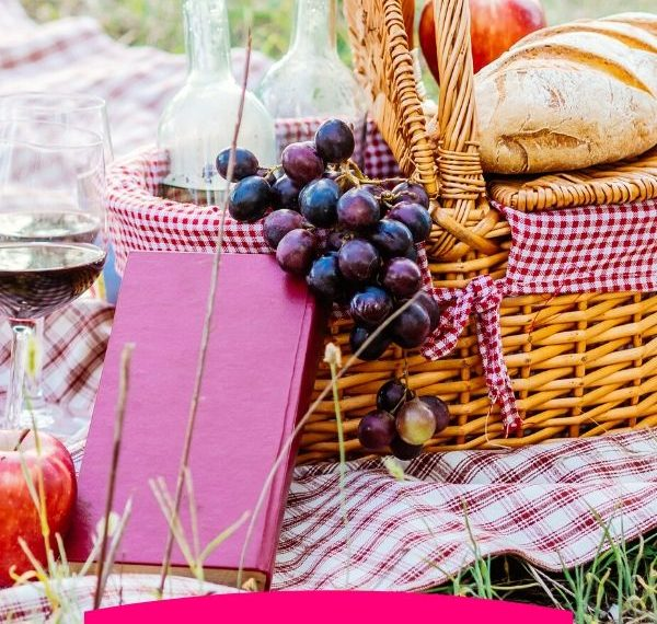 a picnic basket with grapes and bread