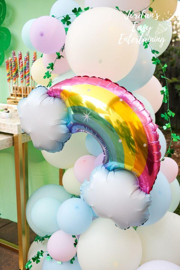 a mylar rainbow balloon on a balloon arch