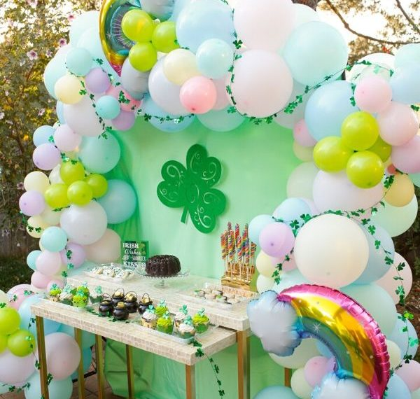 a St. Patrick's day party dessert table with a pastel colored balloon arch