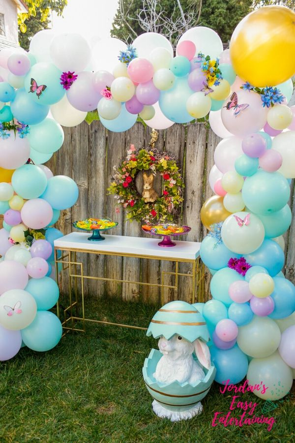 a diy balloon garland with flowers and butterflies