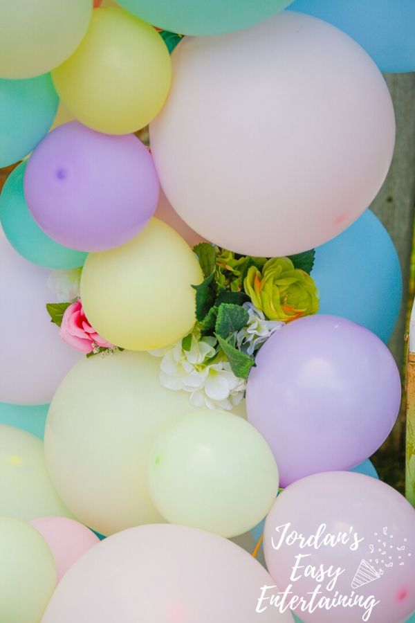 faux flowers tucked into a homemade balloon arch