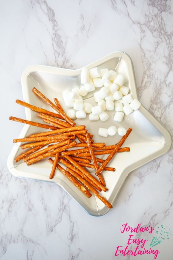 a star shaped plate full of marshmallows and pretzels to make some fun space crafts for kids