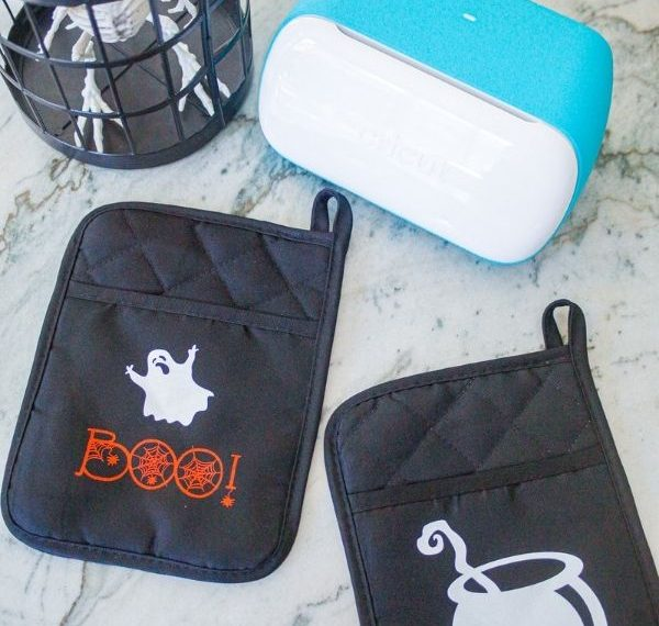 Dollar Tree pot holders with a ghost and the word boo and one with a cauldron and a Cricut Joy machine