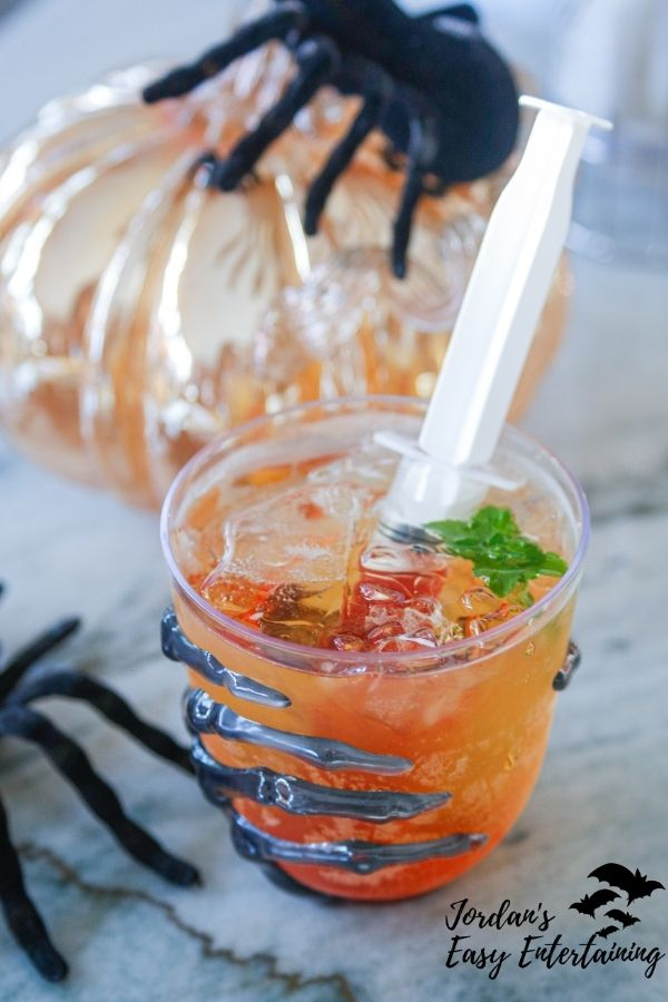 A Halloween cocktail served in a skeleton hand glass with a syringe filled with blood orange syrup