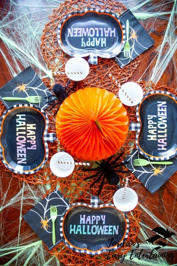 a Halloween tablescape for kids with black pumpkin plates