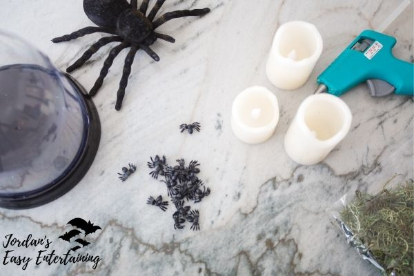 everything needed to make a diy Halloween decoration - battery opereated candles, a glue gun, moss, and a Halloween cloche