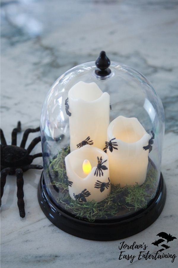 a Halloween candle centerpiece with spiders and moss in a cloche